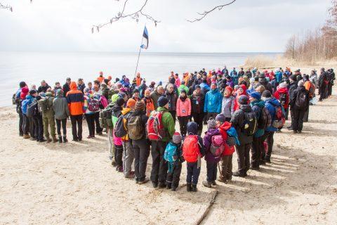 """В Раннапунгерья несколько сотен участников похода образуют на береговом песке цифру """"100"""", которую снимают два дрона."""